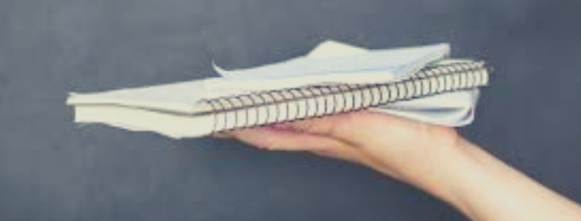 person's hand holding small stack of notebooks and loose paper against gray background